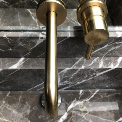 La vasque en marbre et la robinetterie doré brossé apportent leur splendeur